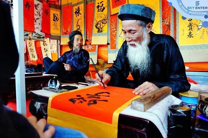 Hình ảnh ông đồ bày mực tàu và giấy đỏ cho chữ đầu năm